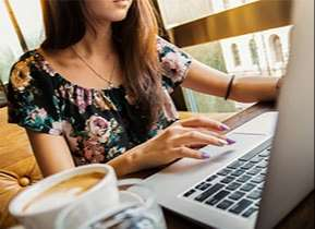 Girl typing on laptop computer with coffee next to her
