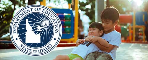 Idaho Department of Education seal with picture of two children sitting in front of playground equipment