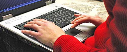 Woman wearing red sweater typing on laptop