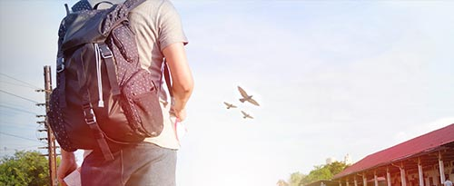 Man standing with backpack with birds in the background