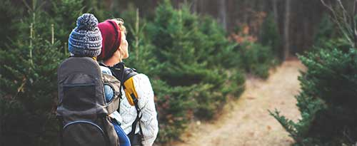 mom carrying child in hiking backpack through trees