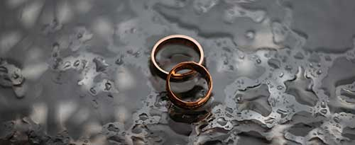 wedding rings on dark table with water