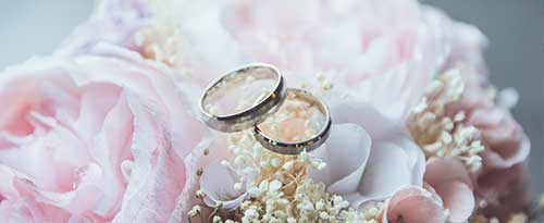 wedding rings on top of flower bouquet