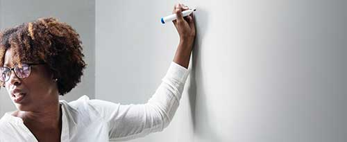 Woman holding marker up to dry erase board